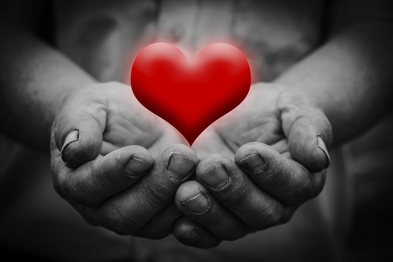 Heart is in the holding hands with dark corners.